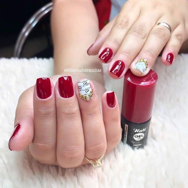 unhas vermelhas decoradas com filha única branca