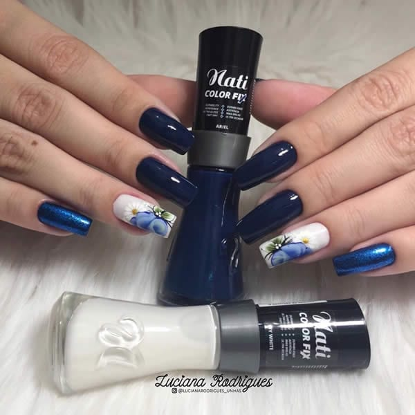 unhas decoradas azuis com uma unha branco com flores e o mindinho com esmaltação azul metálica