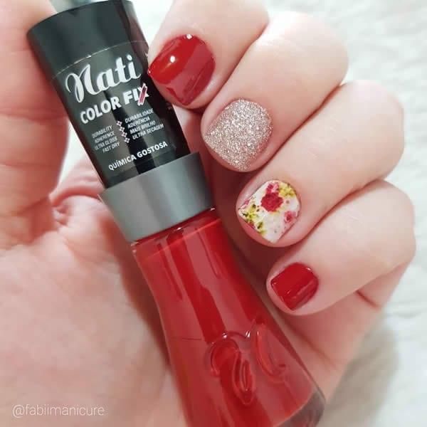 unhas decoradas curtas, com duas unhas de vermelho, uma com glitter prata e outra com adesivo floral