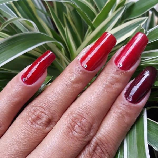 unhas decoradas multicolor com cada unha pintada com um tom diferente de vermelho
