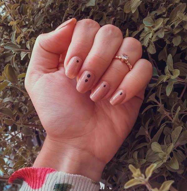 unhas decoradas curtas e delicadas, com esmalte nude contilante e pontinhos pretos minimalistas no centro superior das unhas