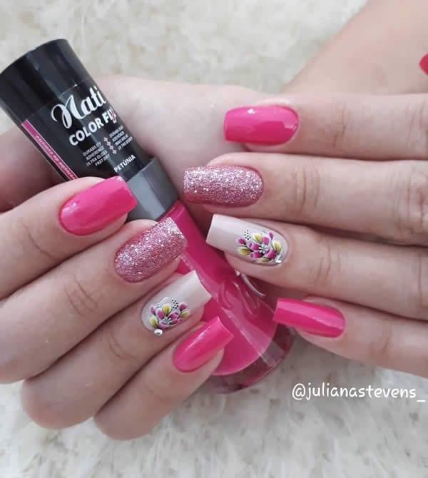 unhas decoradas com três unhas derosa pink, uma unha com glitter rosa e uma unhas com branco e flores