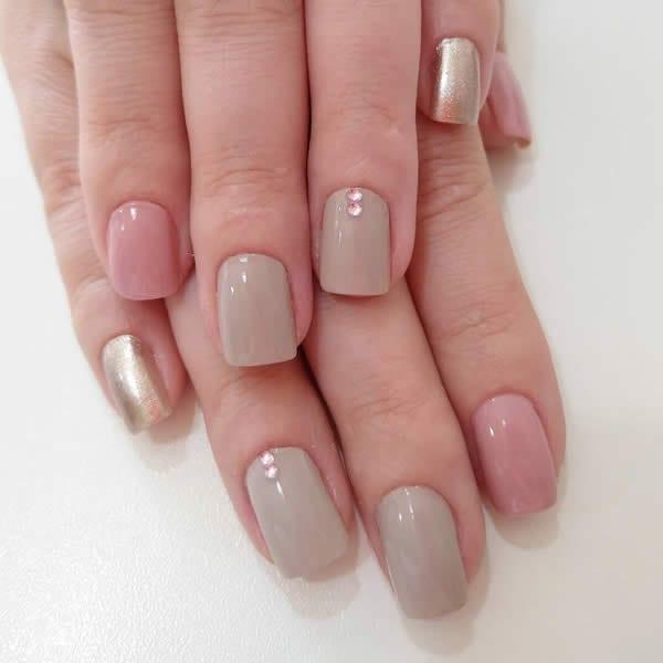 unhas decoradas simples com duas unhas esmaltadas de nude, duas de rosa nude e o mindinho com dourado metálico