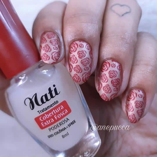 esmaltação fosca com base nude cintilante e flores vermelhas carimbadas